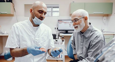 An older man listening to a dentist explain the preliminary treatments he might need to receive dental implants