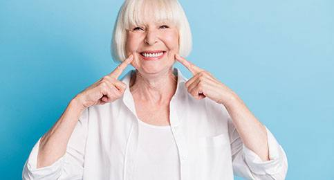An older woman wearing white points to her healthy smile thanks to dental implants