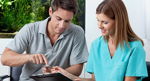 A male patient and female dental employee discussing alternative payment options