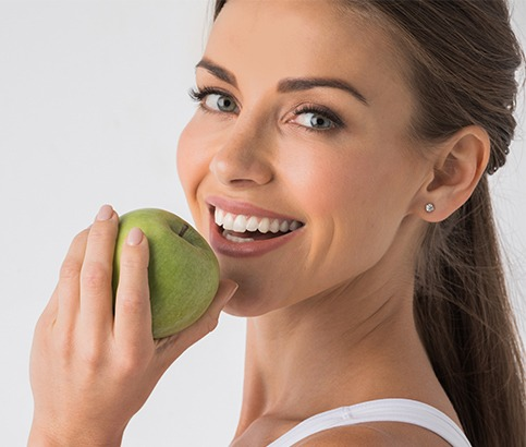 Woman eating an apple after dental implant tooth replacement